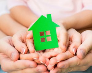 family-hands-holding-green-paper-house