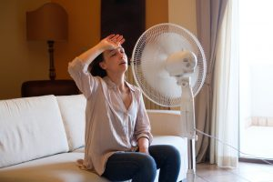 woman-trying-to-cool-down-with-fan